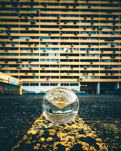 Close-up of crystal ball on glass of building