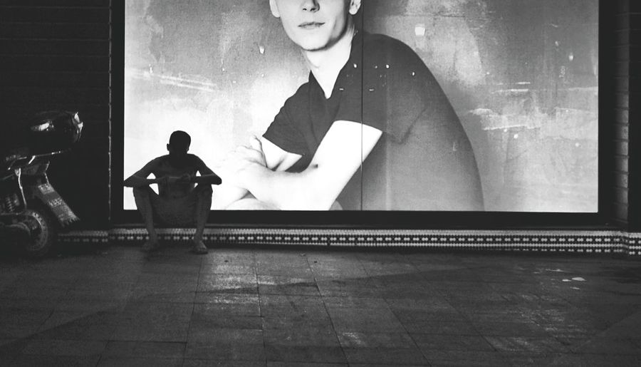 Man sitting against illuminated billboard