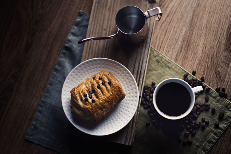 Balck coffee and croissant bread breakfast Breakfast Coffee Coffee Time Kettle Pouring Kettle Steam Wood Afternoon Tea Aroma Bread Brunch Cafe Close-up Coffee - Drink Coffee Beans Coffee Break Coffee Cup Croissant Dark Background High Angle View Mug Retro Styled Swan Neck Kettle Table Top View
