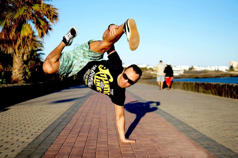 Young Man Practicing Handstand On Footpath