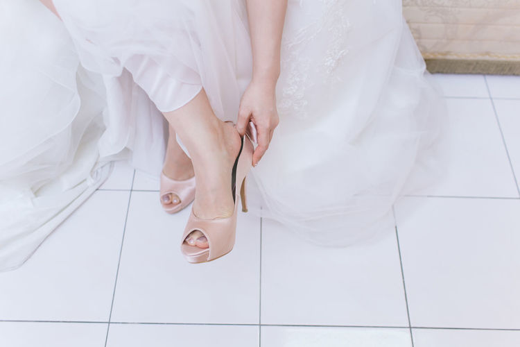 Low section of bride wearing sandal on floor