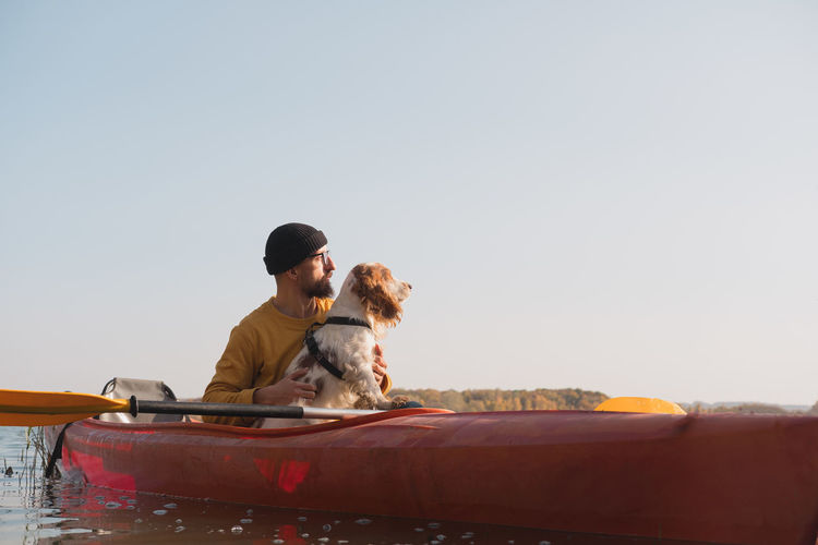 Man with dog sitting in boat against clear sky