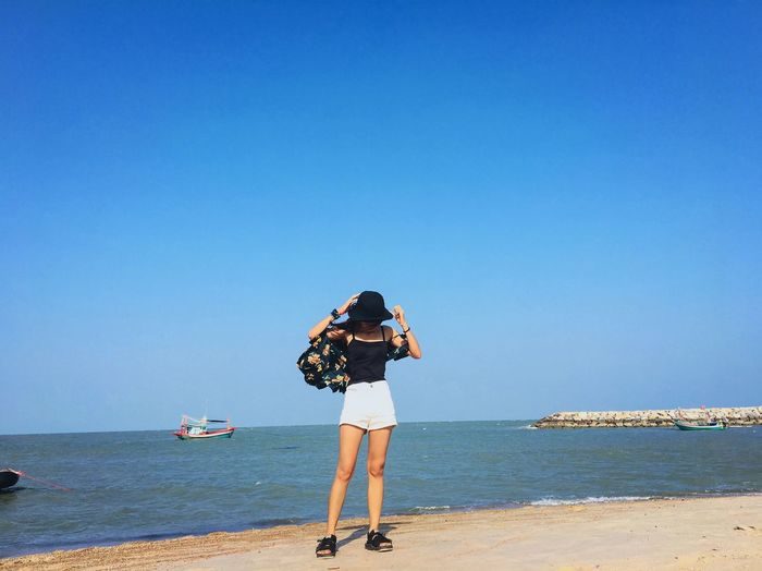 Full length of woman standing at beach against clear blue sky