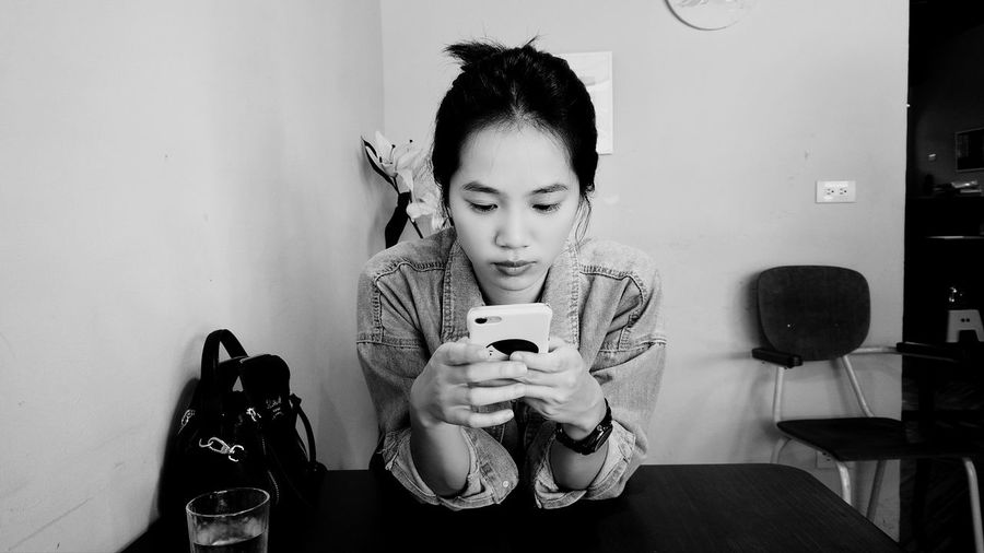 Young woman using mobile phone on table