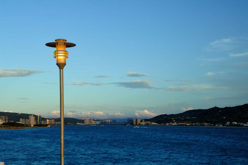 Street light by sea against buildings in city
