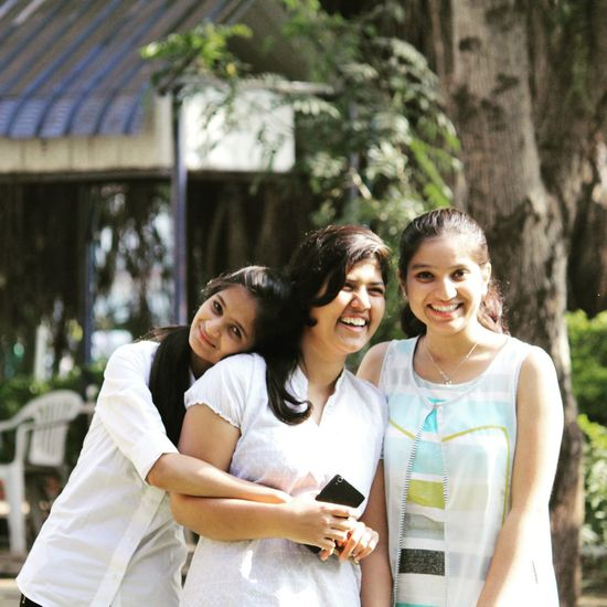 Smiling young women using smart phone outdoors