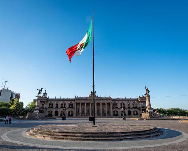 Flag against blue sky in city