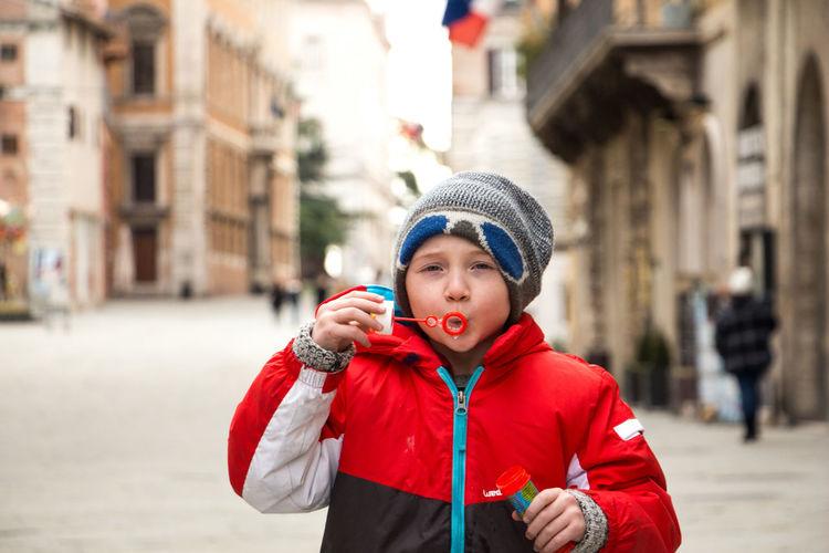 Portrait of boy wearing hat standing in city
