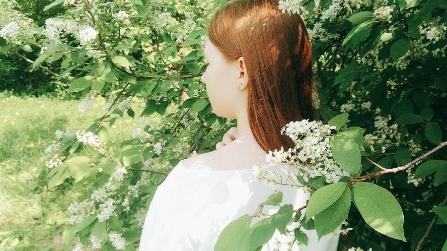 Rear view of teenage girl by flowering plants