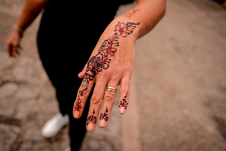 High angle view of woman hand with tattoo