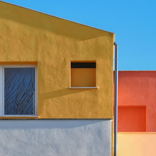 Low angle view of house against clear blue sky