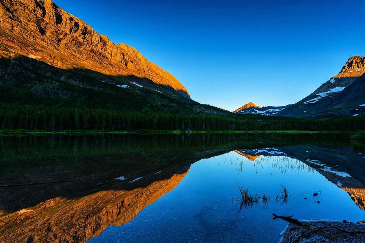 Mirror, mirror. Sunrise in Glacier National Park's Swiftcurrent Lake. EyeEm Selects Water Reflection Lake Scenics - Nature Sky Beauty In Nature Mountain Tranquility Nature Tranquil Scene Blue Non-urban Scene No People Waterfront Reflection Lake Mountain Range Idyllic Clear Sky The Great Outdoors - 2018 EyeEm Awards
