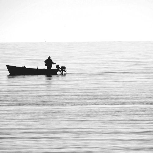 Silhouette Man In Boat On Sea Against Clear Sky