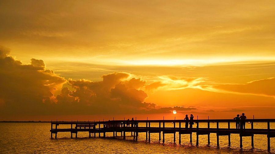 Silhouette pier on sea against orange sky during sunset