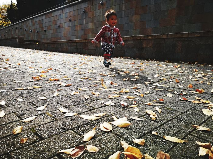 Boy running on footpath and leaves during autumn