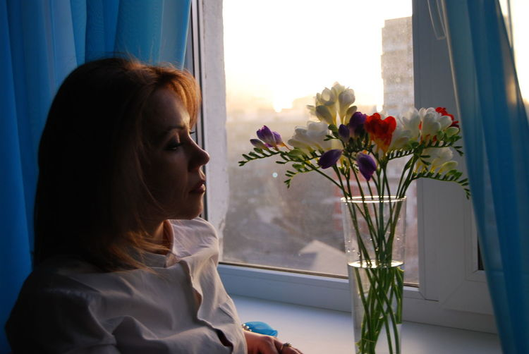 Woman looking at flower vase against window at home