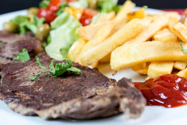 Close-up of meat with french fries in plate