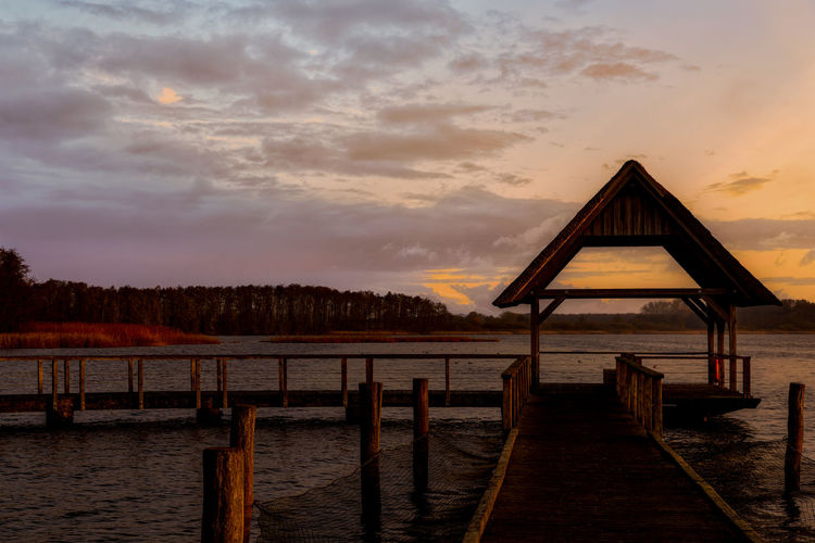 Wooden pier over lake against sky during sunset