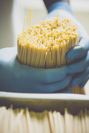Cropped image of worker holding spaghetti in factory