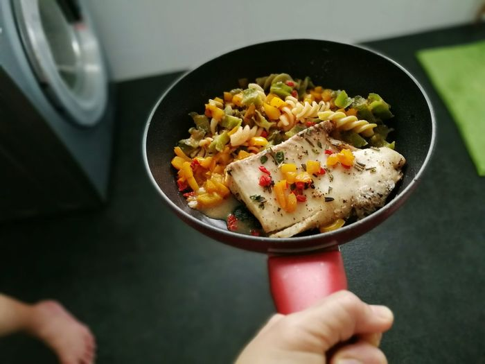 Cropped Hand Of Person Holding Pasta In Cooking Pan At Home