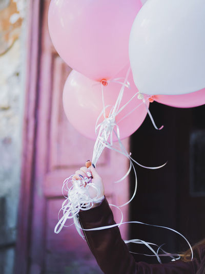 Close-up of hand holding balloons against pink door