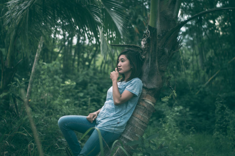 Palm Tree Fashion Stories Alone Alone Time Asian  Daydream Woman Beautiful Woman Beauty In Nature Casual Clothing Day Daydreaming Forest Full Length Nature One Person Outdoors People Plant Real People Side View Sitting Tree Women Young Adult Young Women Leisure Activity Lifestyles