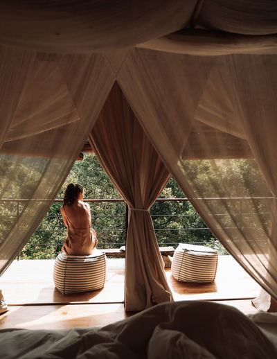 Girl at luxury tree hut Sitting Lifestyles Women Adult Curtain Relaxation Architecture Nature Luxury Full Length Travel Sunlight Tree Hut Resort Dreamy View Jungle Girl Travel Sri Lanka Living Heritage White Earth Colors Koslanda