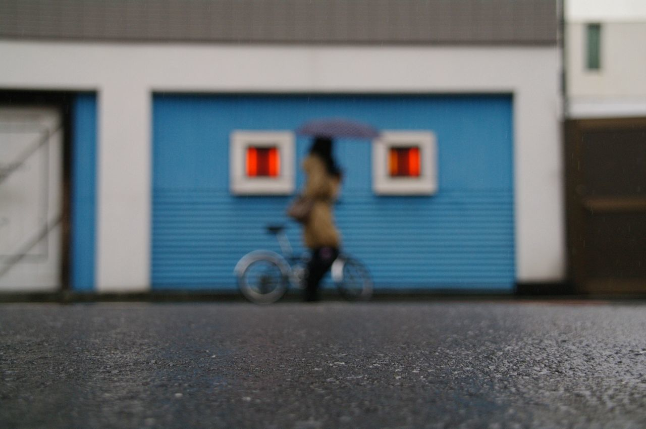 Surface level of woman with bicycle walking against house