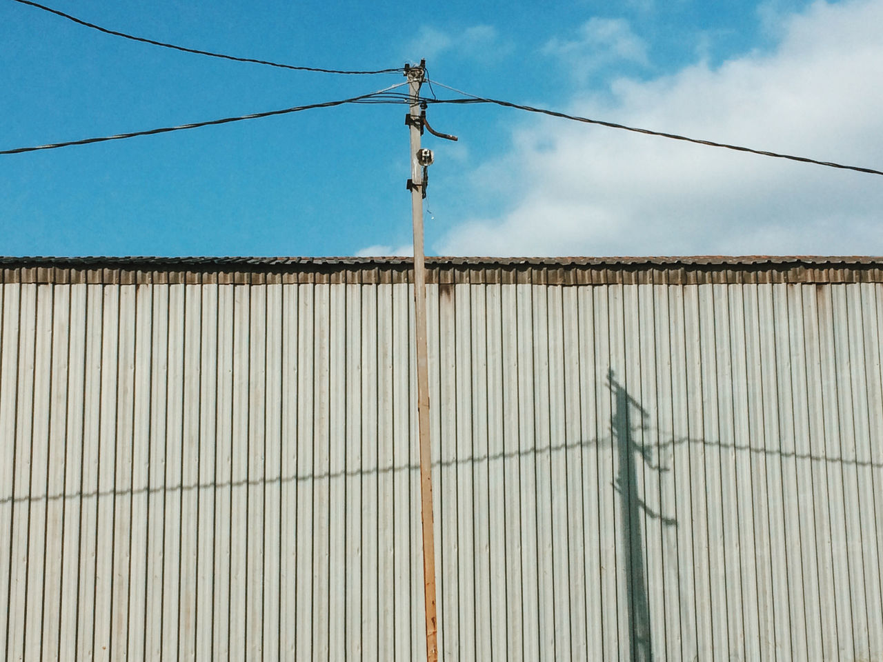 Low angle view of corrugated iron against sky