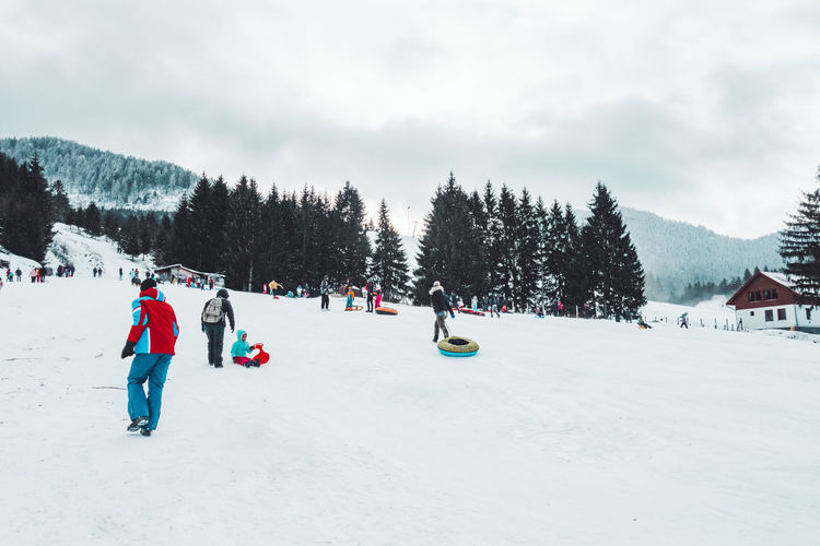 Fun in winter land Snow Tree Winter Cold Temperature Plant Sky Land Nature Day Outdoors Slope Mountain Mountain Range Vacation Vacations Holiday Wintertime Winter Winter Wonderland Fun Snowcapped Mountain Family Time Sony Rx100 Pine Tree Scenery