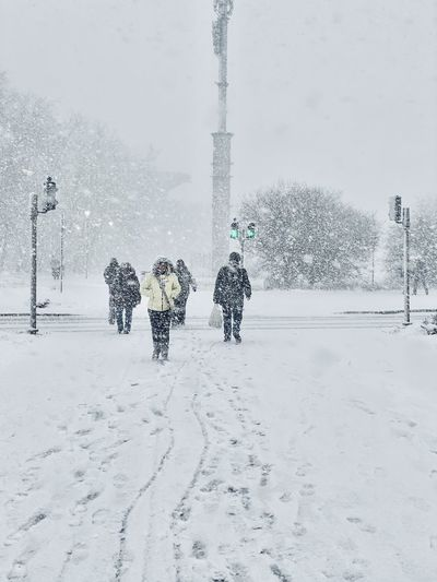People walking on snow covered field during winter