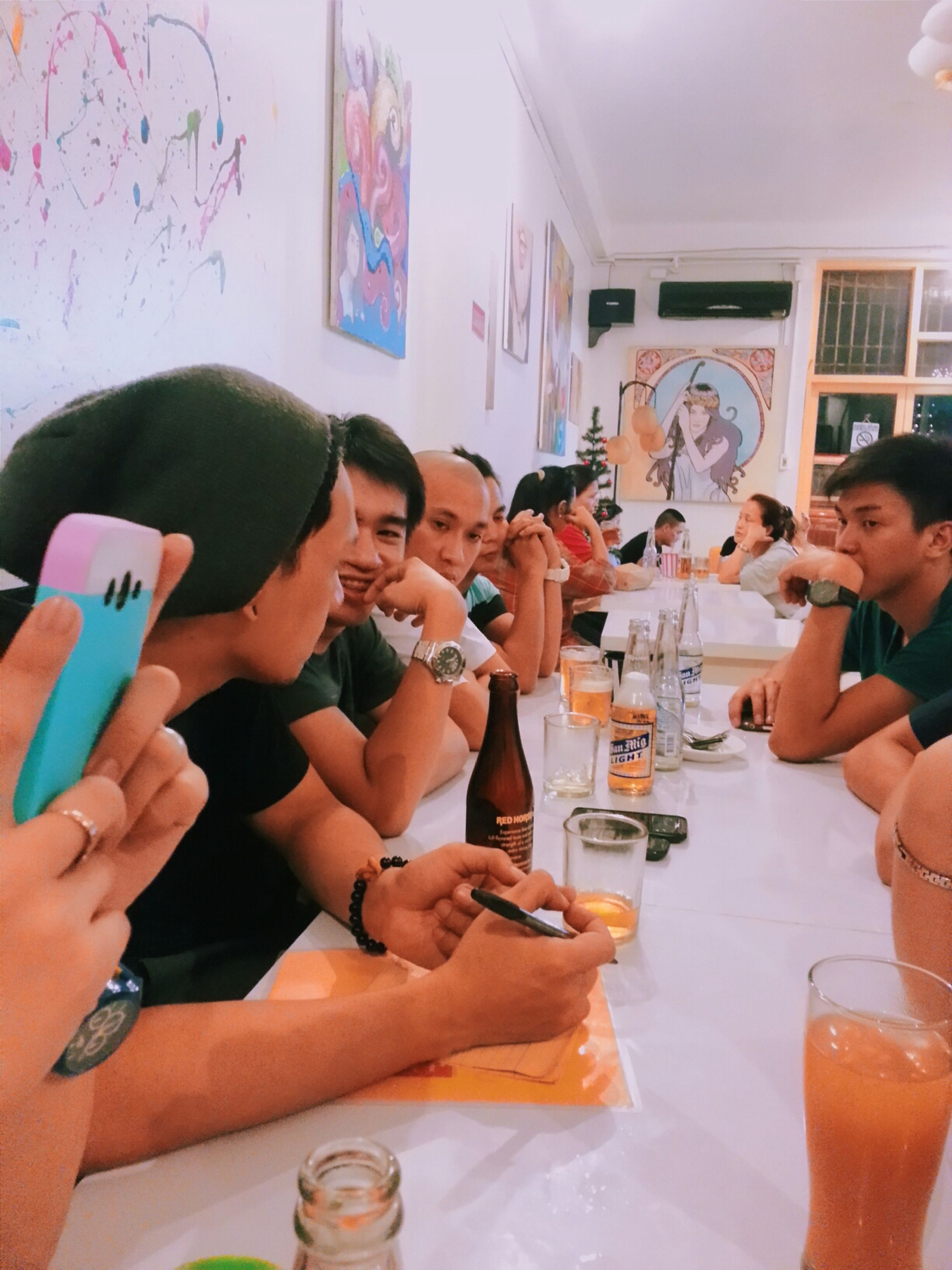 indoors, lifestyles, leisure activity, person, holding, young adult, casual clothing, young women, happiness, food and drink, smiling, table, togetherness, sitting, communication