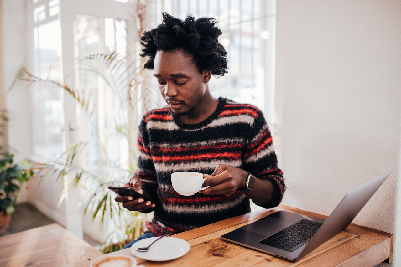 Man using phone while having coffee in cafe