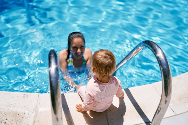 High angle view of woman looking at swimming pool