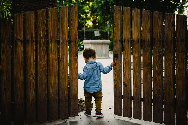 Rear view of boy standing by gate against fence