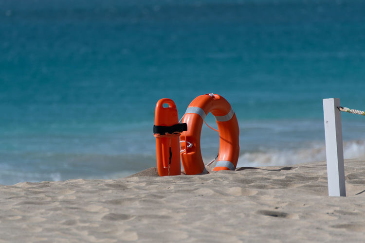 Hoffi99 Water Sea Land Beach Nature Day Red Sunlight Protection Security Beauty In Nature Orange Color Outdoors Safety No People Horizon Over Water Sand Tranquility Blue