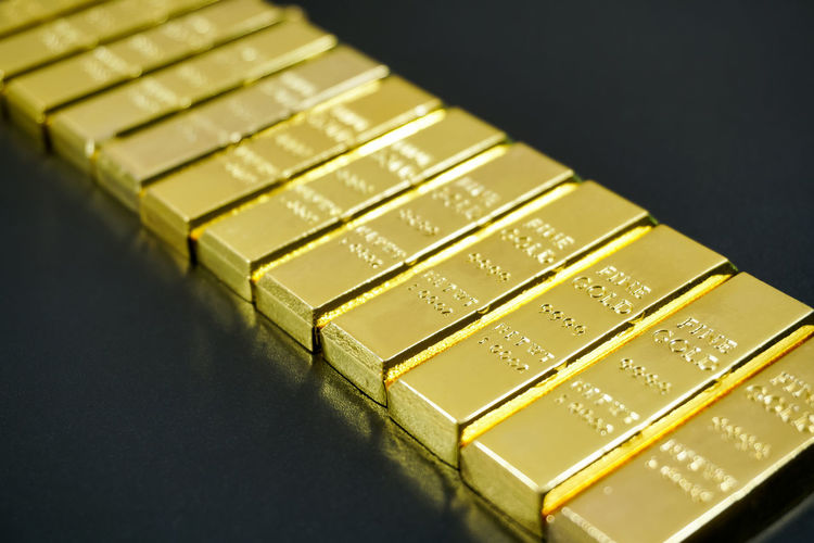 Close-up of gold bars in row on table