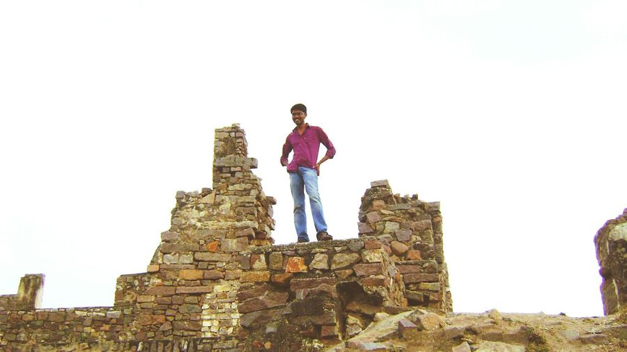 Low Angle View Of Man Standing On Wall At Golconda Fort Against Sky