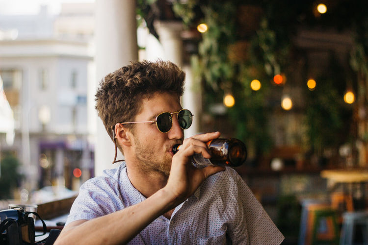 Young man drinking beer at restaurant
