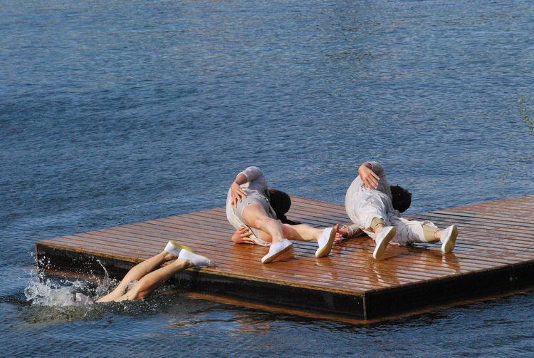 Artists performing on diving platform over lake