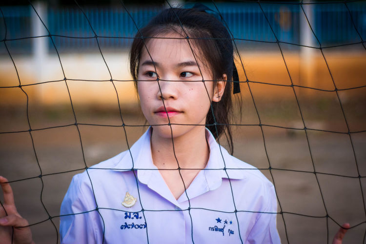 Thoughtful young woman standing behind net
