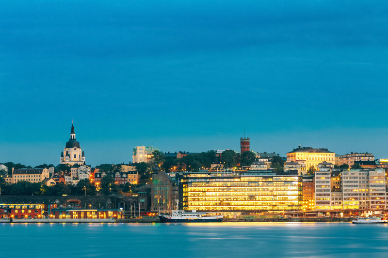 Embankment In Old Part Of Stockholm At Summer Evening, Sweden Yellow Water Travel Tourism Sweden Summer Sky Ship Sea Scandinavia River Reflection Place Panorama Night Light Landscape Illuminated Famous Evening Embankment Colorful Cityscape City Blue Architecture Stockholm