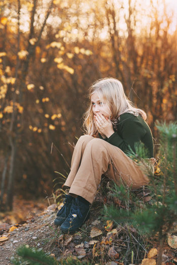 A beautiful teenage girl with blond hair sits thoughtfully in an autumn park, warms her hands