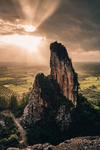 Rock formations on landscape against sky during sunset