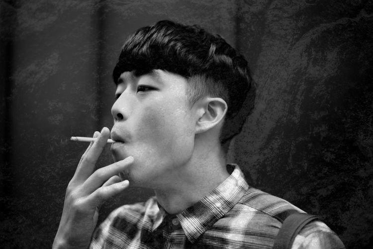 Man smoking cigarette against wall
