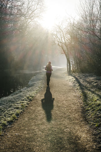 Rear view full length of woman jogging by canal on road during sunny day