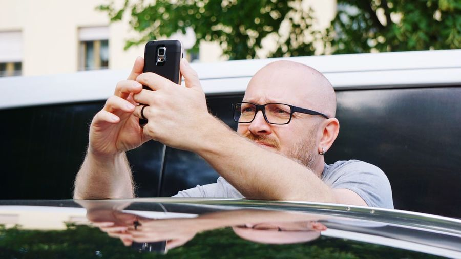 Close-up of man wearing eyeglasses using mobile phone by car