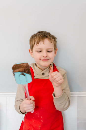 Chocolate Batter Boy In Kitchen Boys Brownies Casual Clothing Child Baking Child Cooking Childhood Day Front View Indoors  Licking Spatula One Person Real People Red Apron Spatula