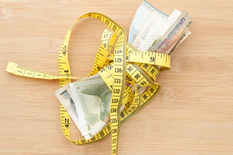 Conceptual Concept Conceptual Wooden Background Money Measurement Measuring Tape Tape Measure Tied Weight Weightloss Slimming Cost Currency Paper Currency Savings Finance Wealth Close-up Making Money Waist