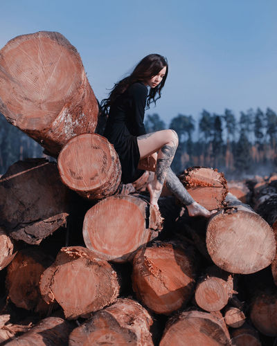 Side view of woman sitting on logs against clear sky